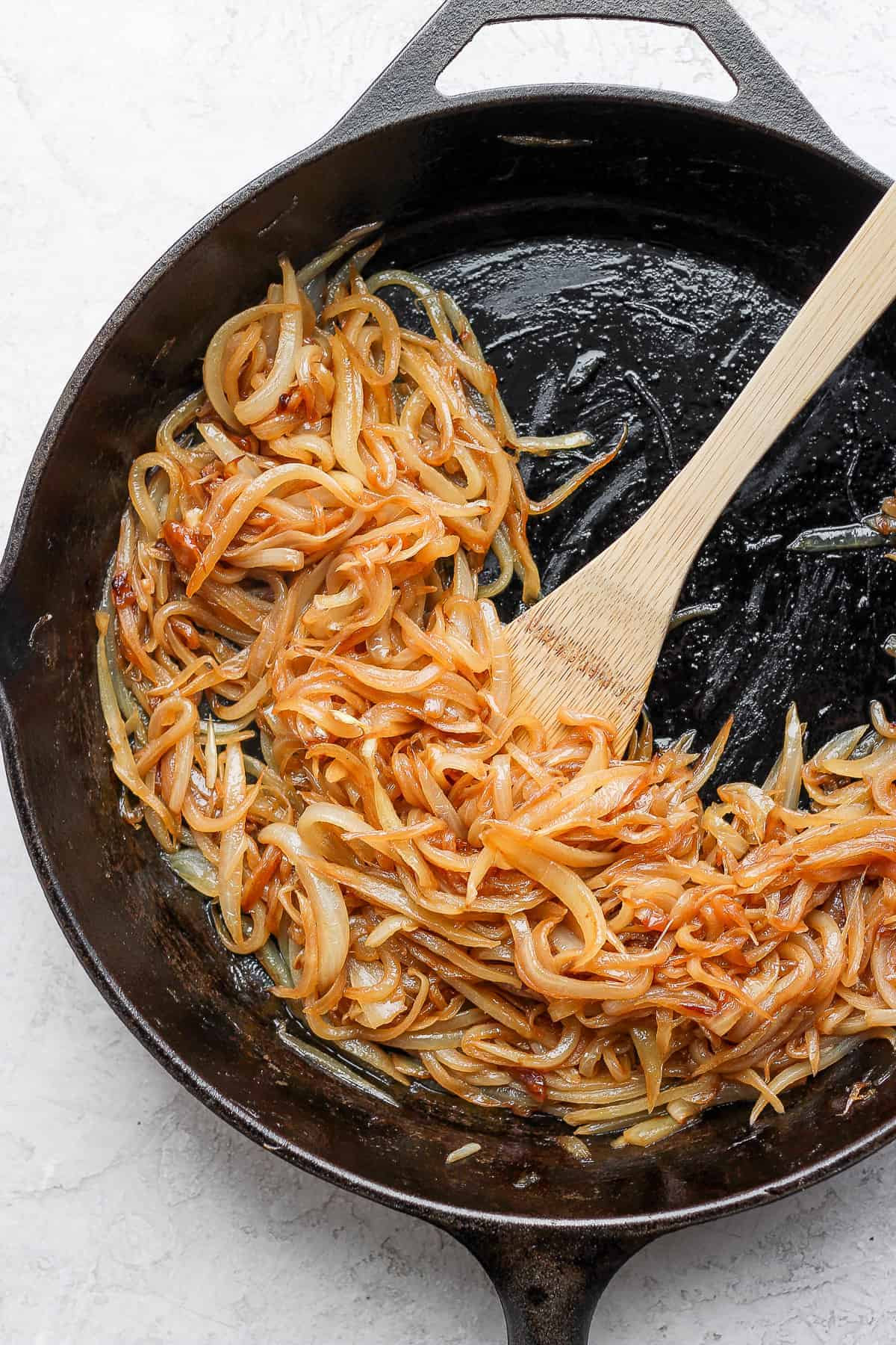 Caramelizing onions on a cast iron skillet with wooden skillet