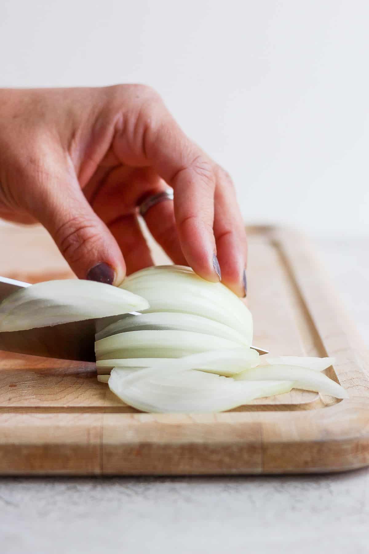 Slicing half an onion on cutting board
