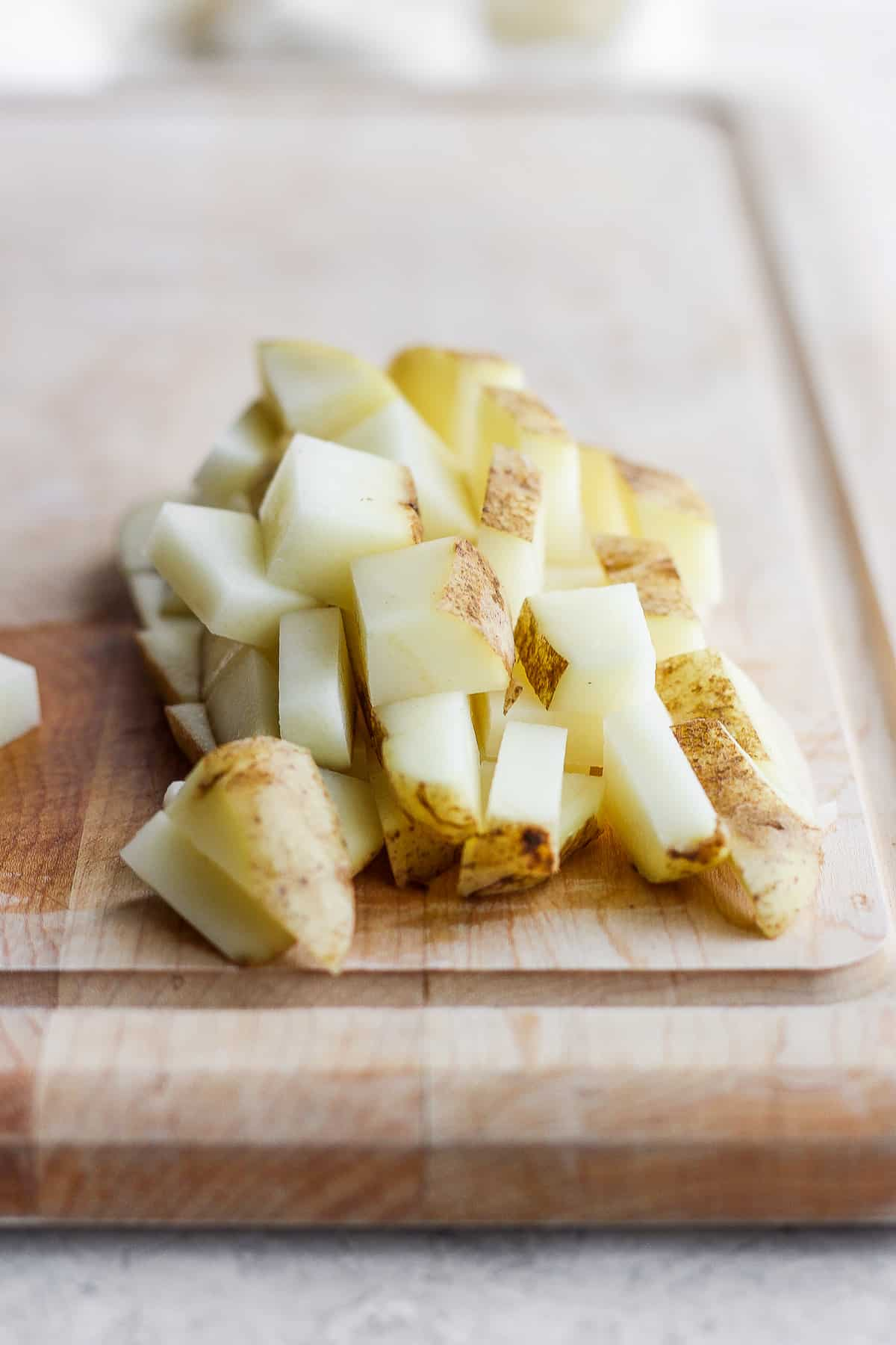 Cubed potatoes cut on a cutting board