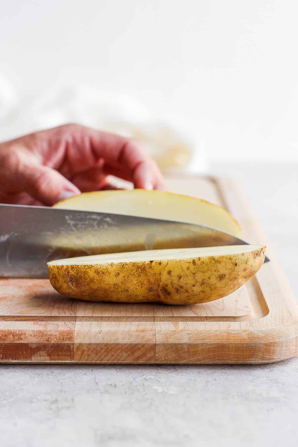 Cutting board with large potato being cut