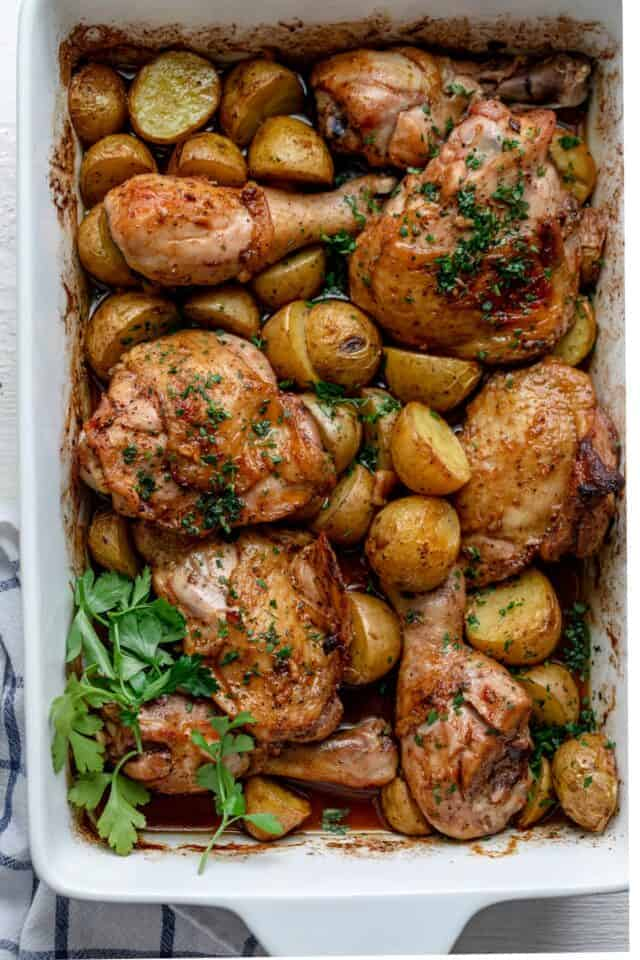 Chicken and potatoes in a pan garnished with parsley