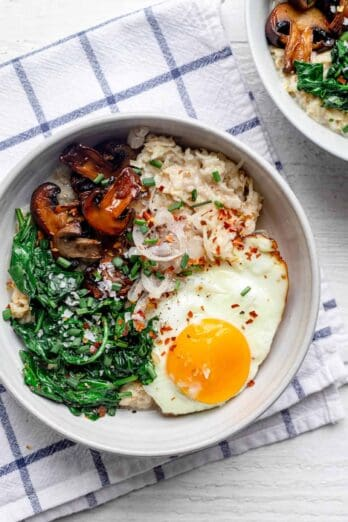 Bowl of savory oatmeal topped with spinach, mushrooms, shallows, and a fried egg