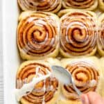 Spoon glazing vegan cinnamon rolls in white pan