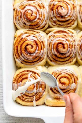 Spoon glazing vegan cinnamon rolls in white pan