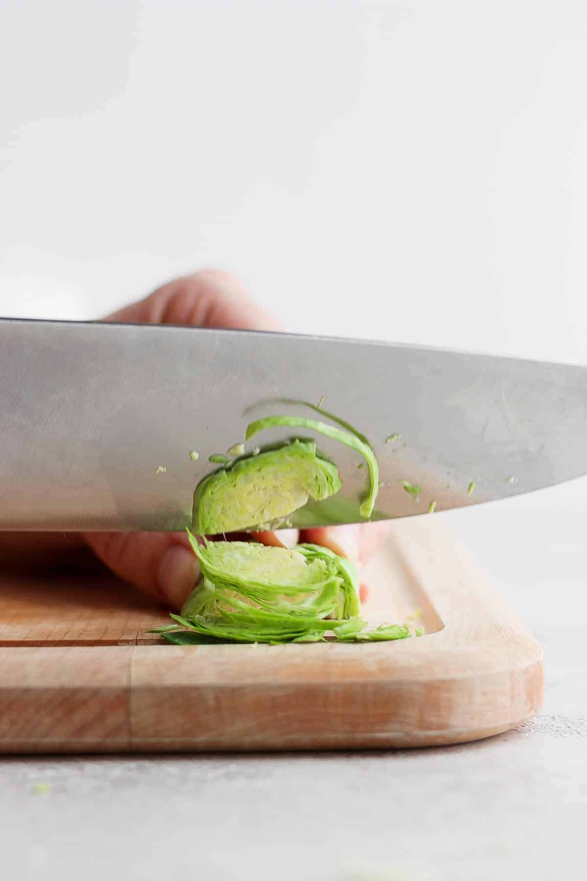 Chef's knife cutting a brussel sprout