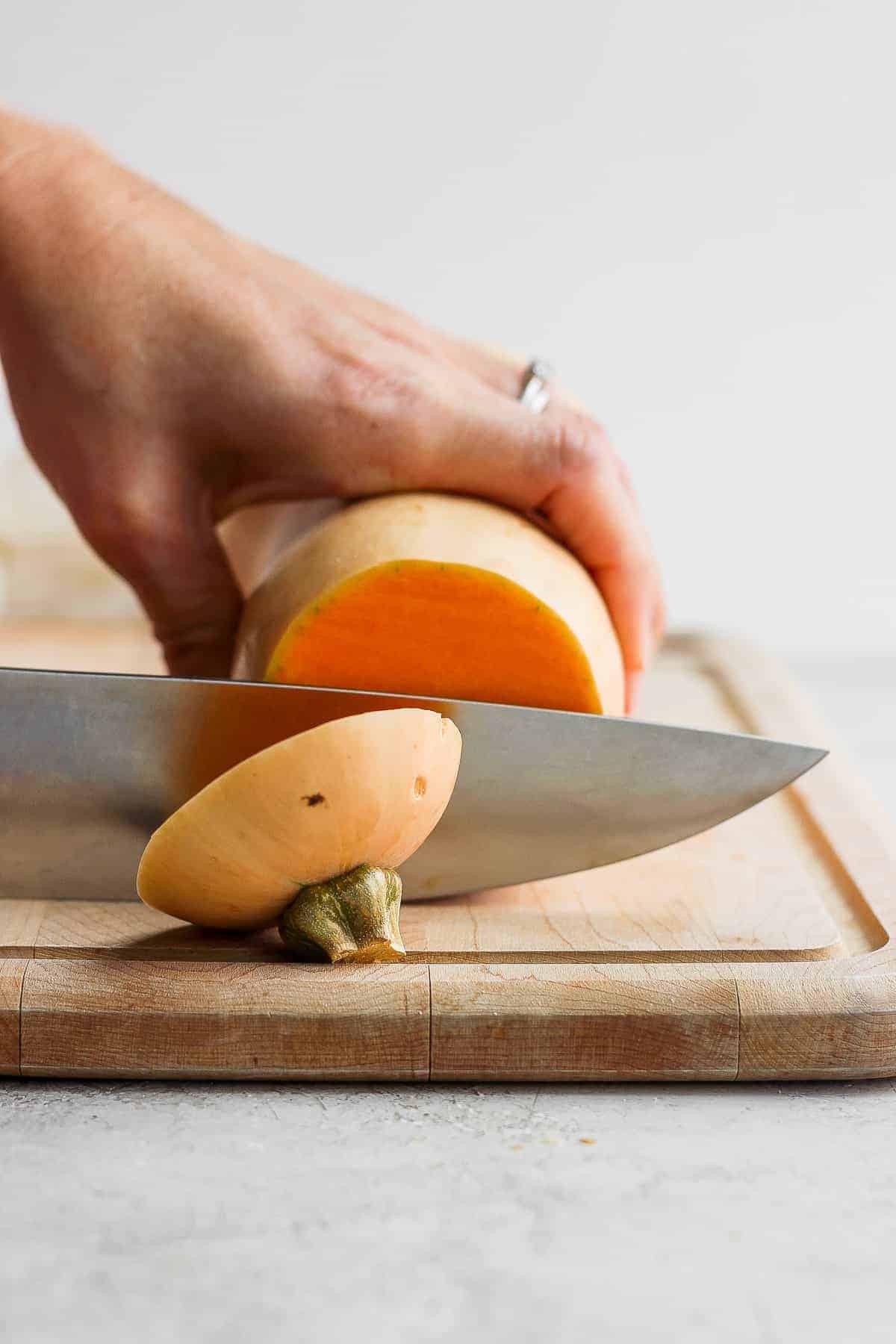 Butternut squash on cutting board getting cut