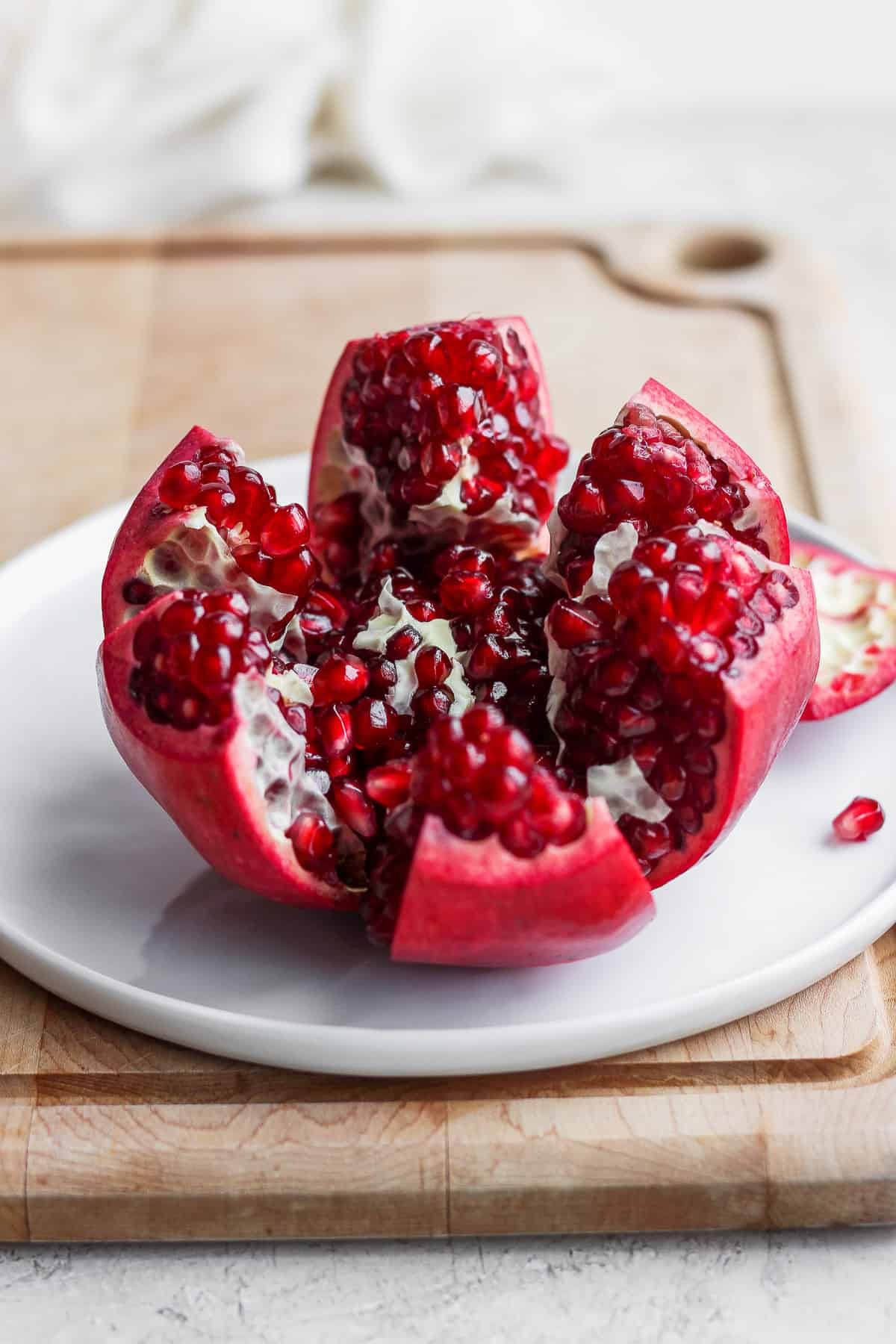 Pomegranate cut into segments on white dish