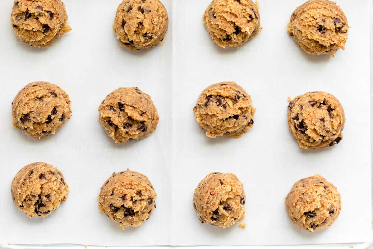 12 cookie dough balls rolled out on parchment paper