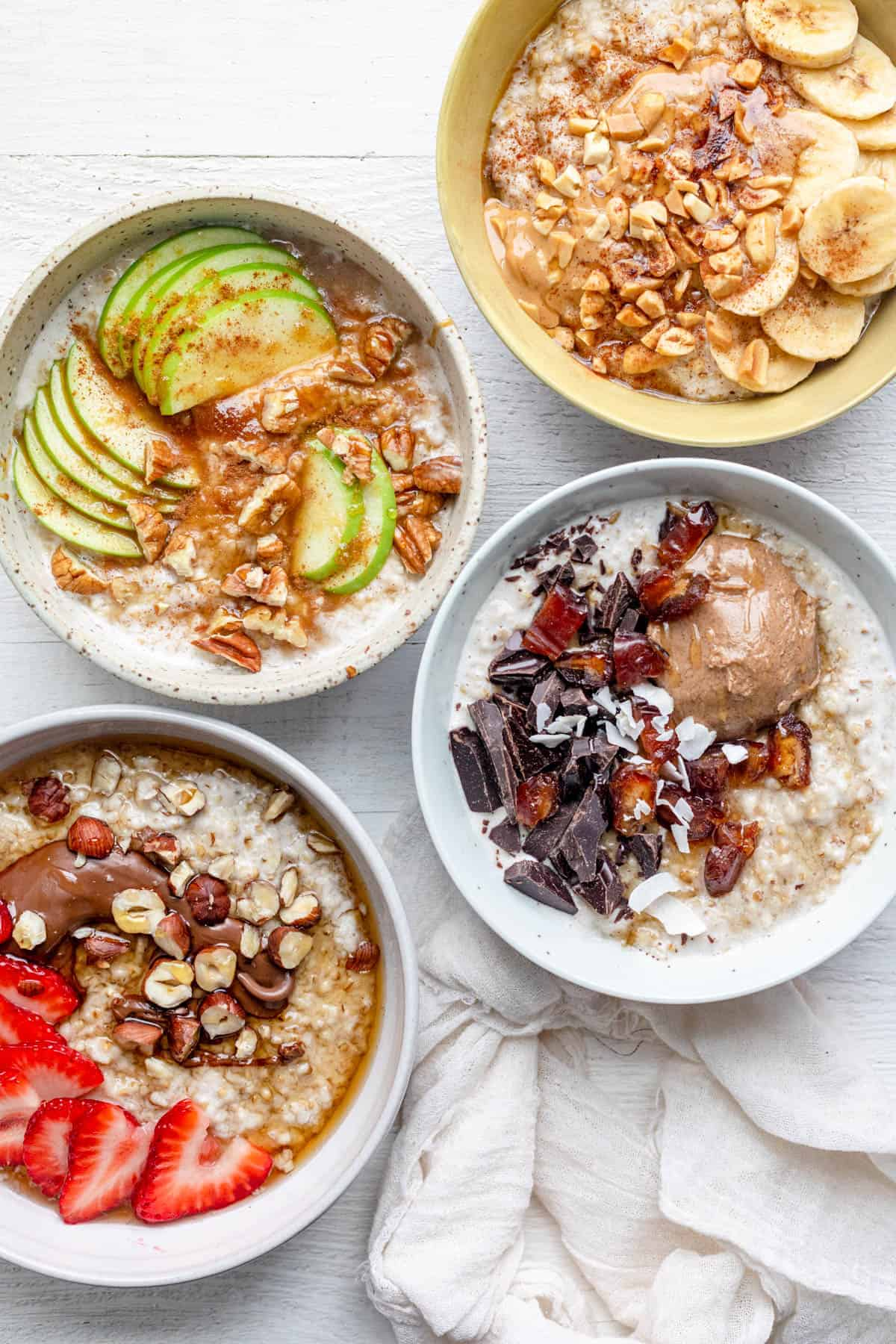 4 varieties of overnight steel cut oatmeal in 4 bowls with different toppings