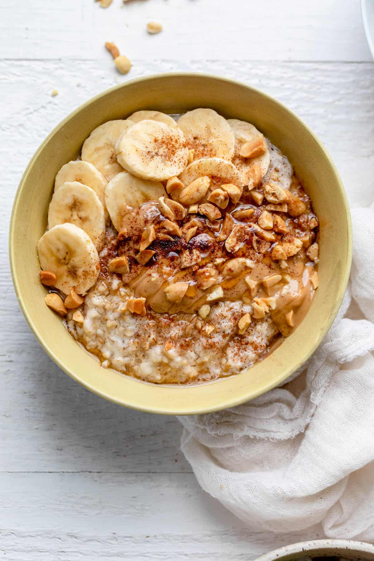 Bananas and peanut butter over oatmeal in yellow bowl