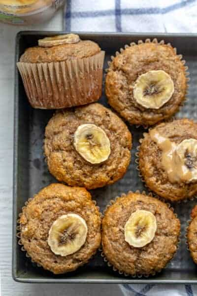 Peanut butter banana muffins in a pan topped with slices of bananas