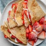 Overhead shot of protein crepes with strawberries and cream on blue napkin