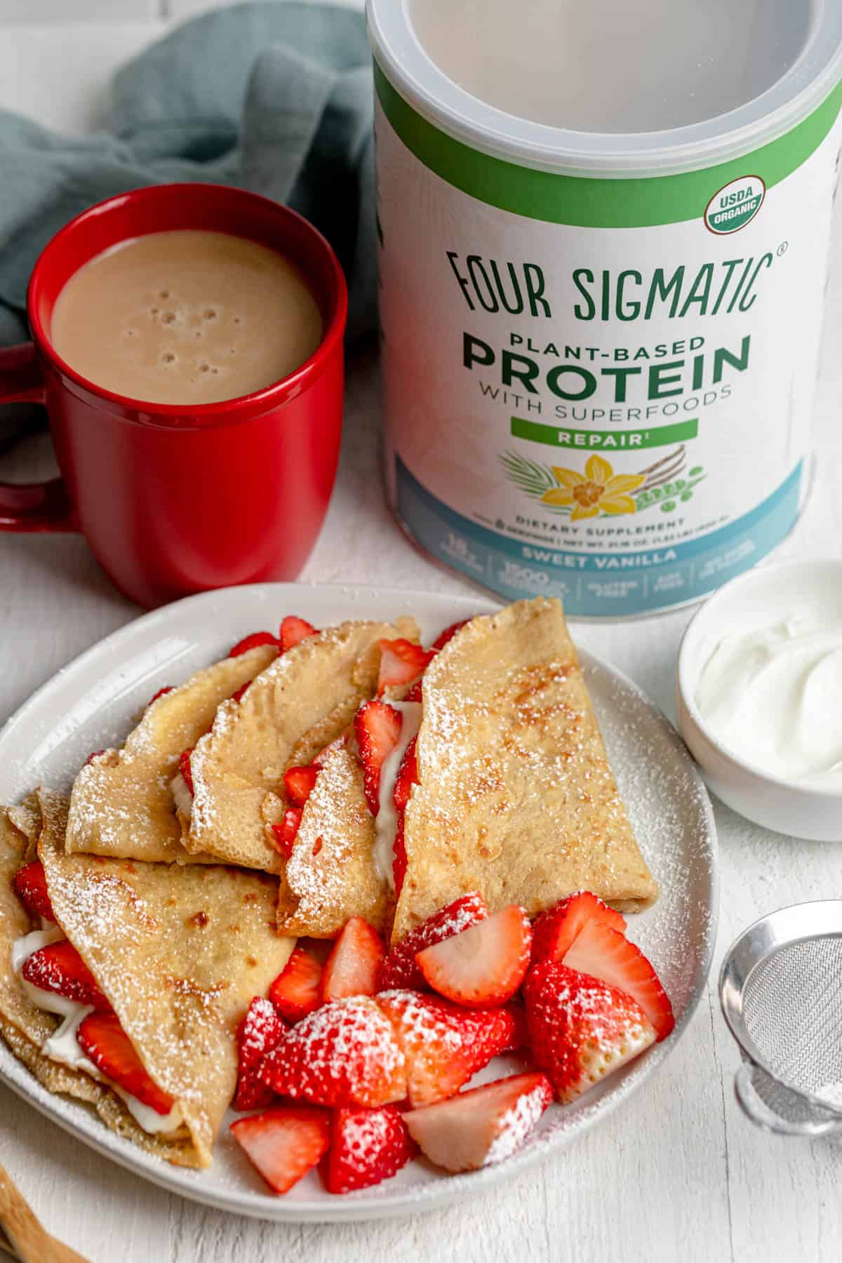 Protein crepes on a plate with strawberries and cream, red coffee mug in background and Four Sigmatic protein powder in background