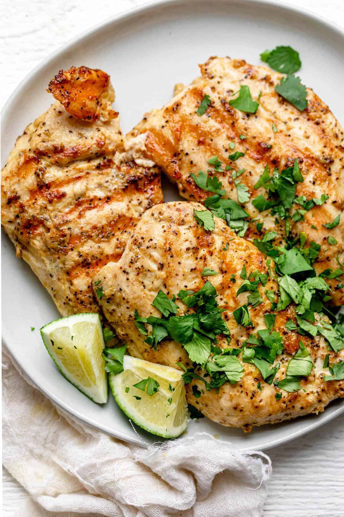 Grilled Dijon chicken on a plate with lime wedges and cilantro