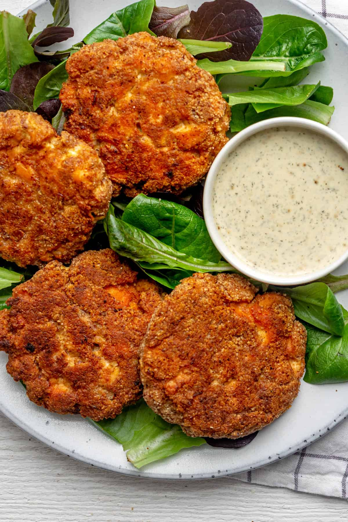 Close up shot of the salmon cakes on bed of greens with dipping sauce