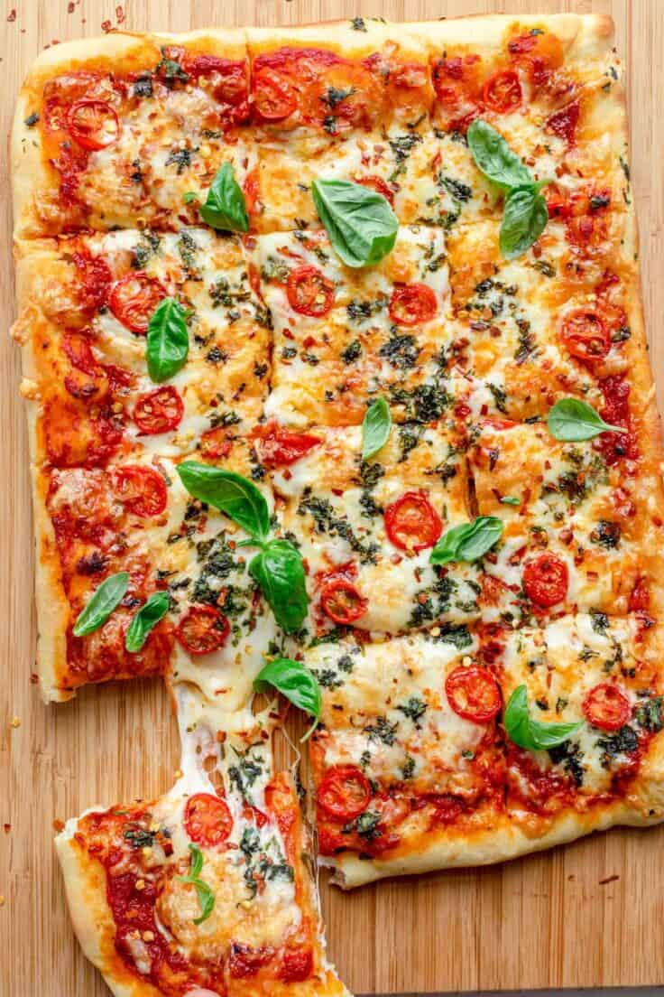 Sheet pan pizza with slice being pulled away