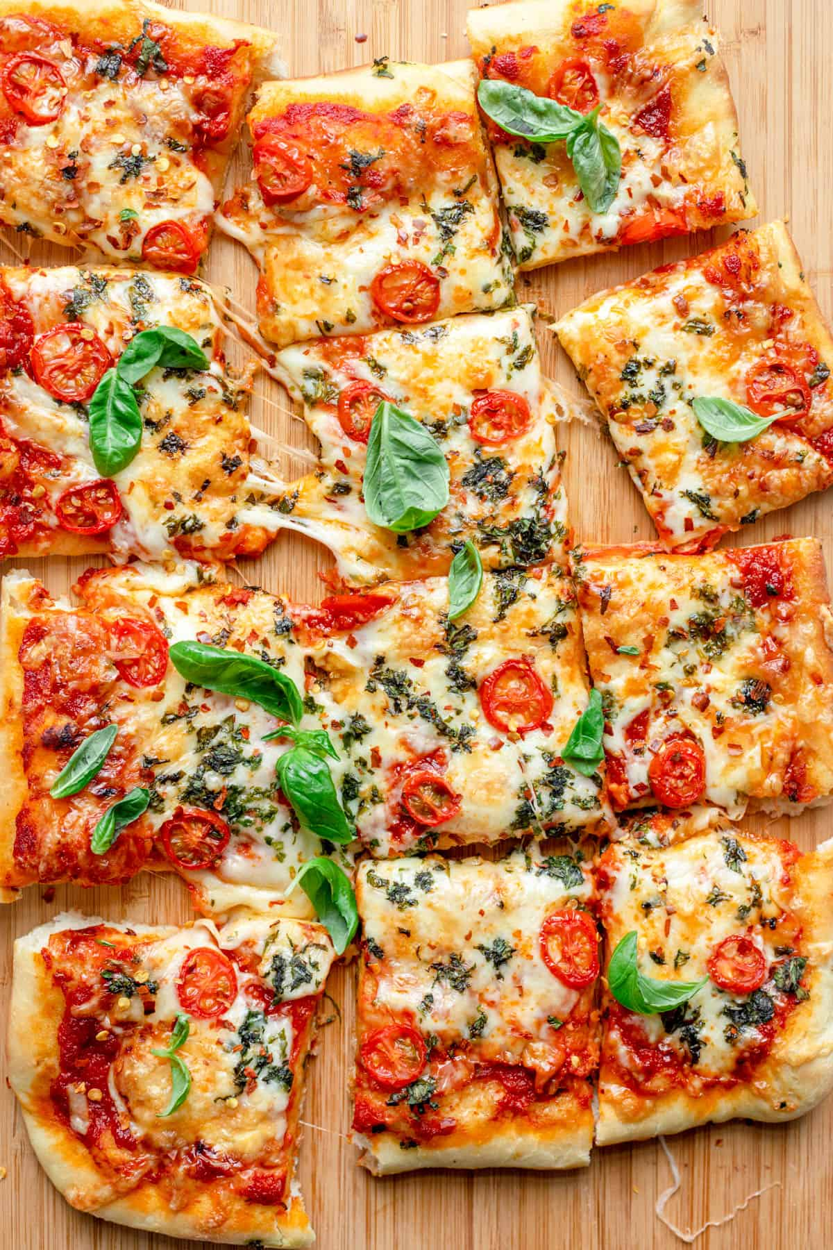 Pizza resting on wooden board, sliced into 12 pieces