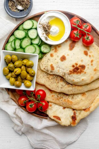 Yogurt flatbread on a board with vegetables and labneh dip