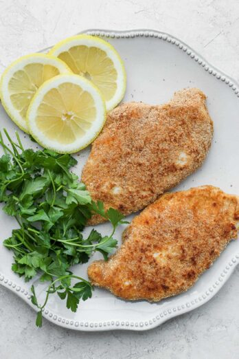 Breaded chicken on plate with parsley and lemon slices