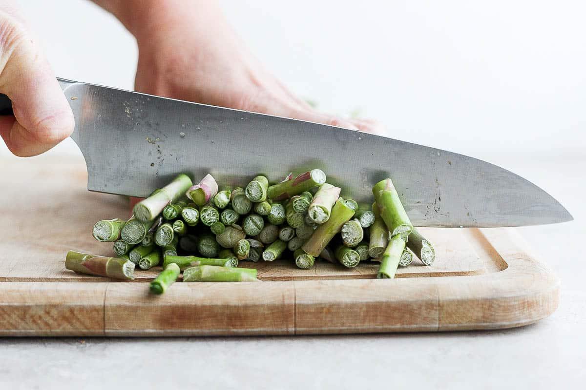 Cutting ends off asparagus on cutting board