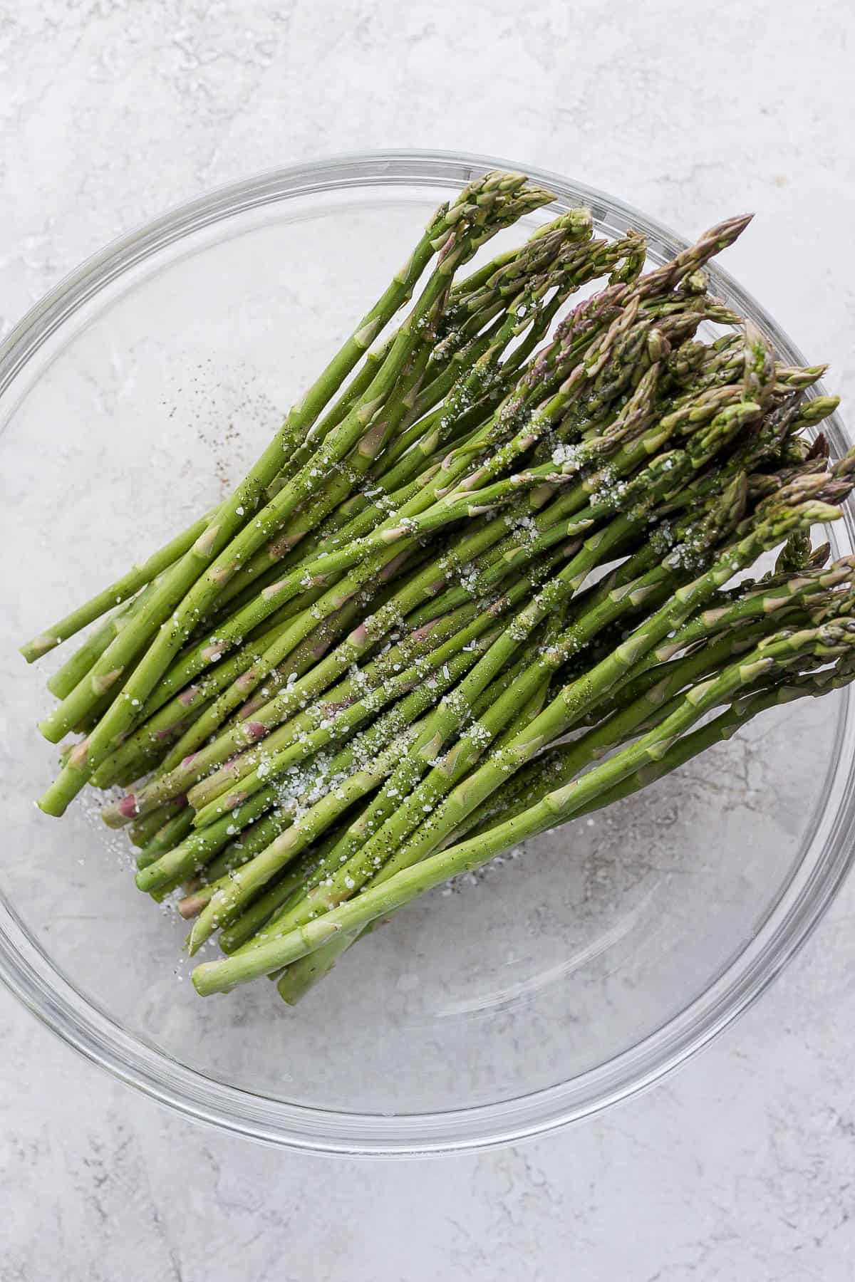 Tossing asparagus with olive oil, salt and papper