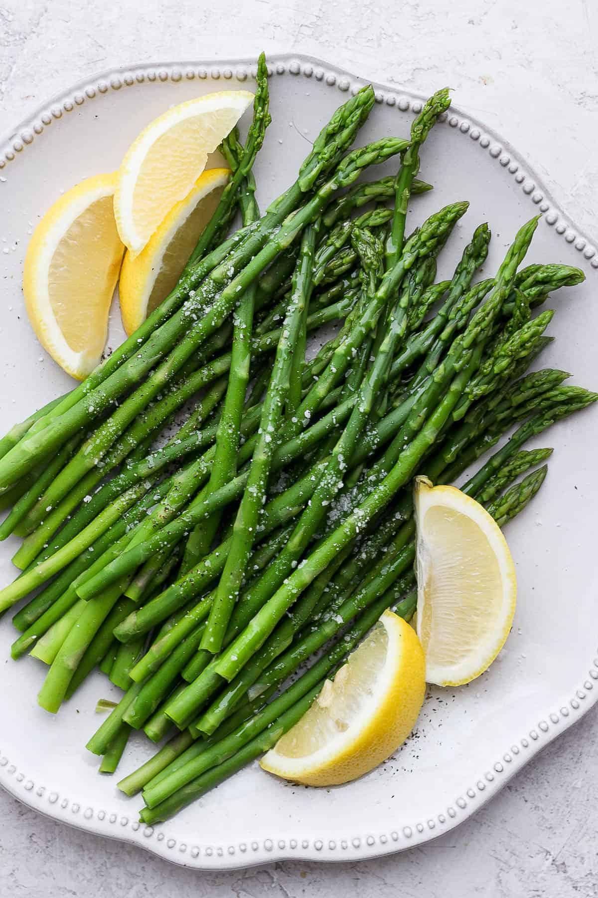 Boiled asparagus on a plate with lemon wedges
