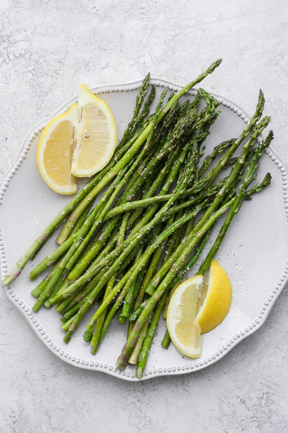 Oven roasted asparagus on a plate with lemon wedges