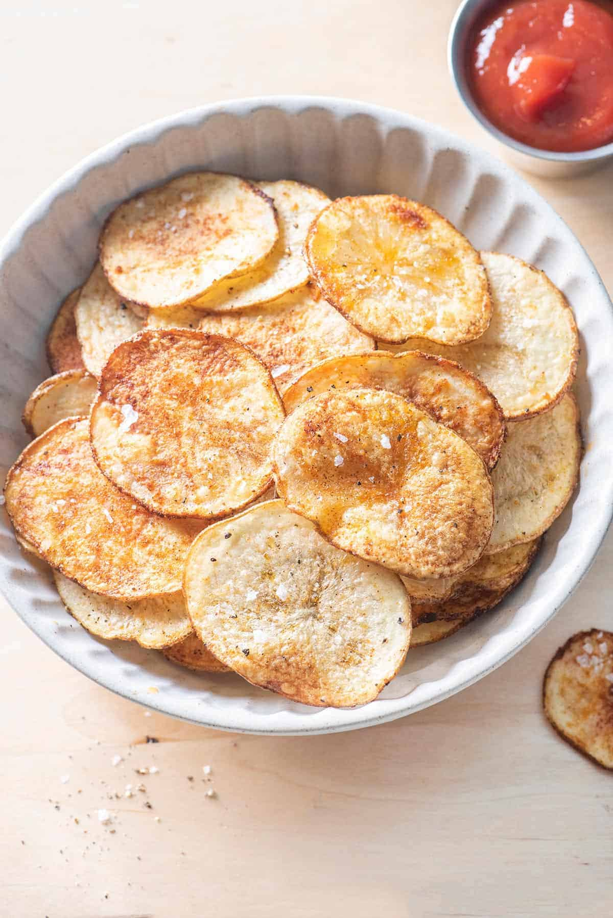 Overhead shot of the oven baked potato chips with ketchup on the side