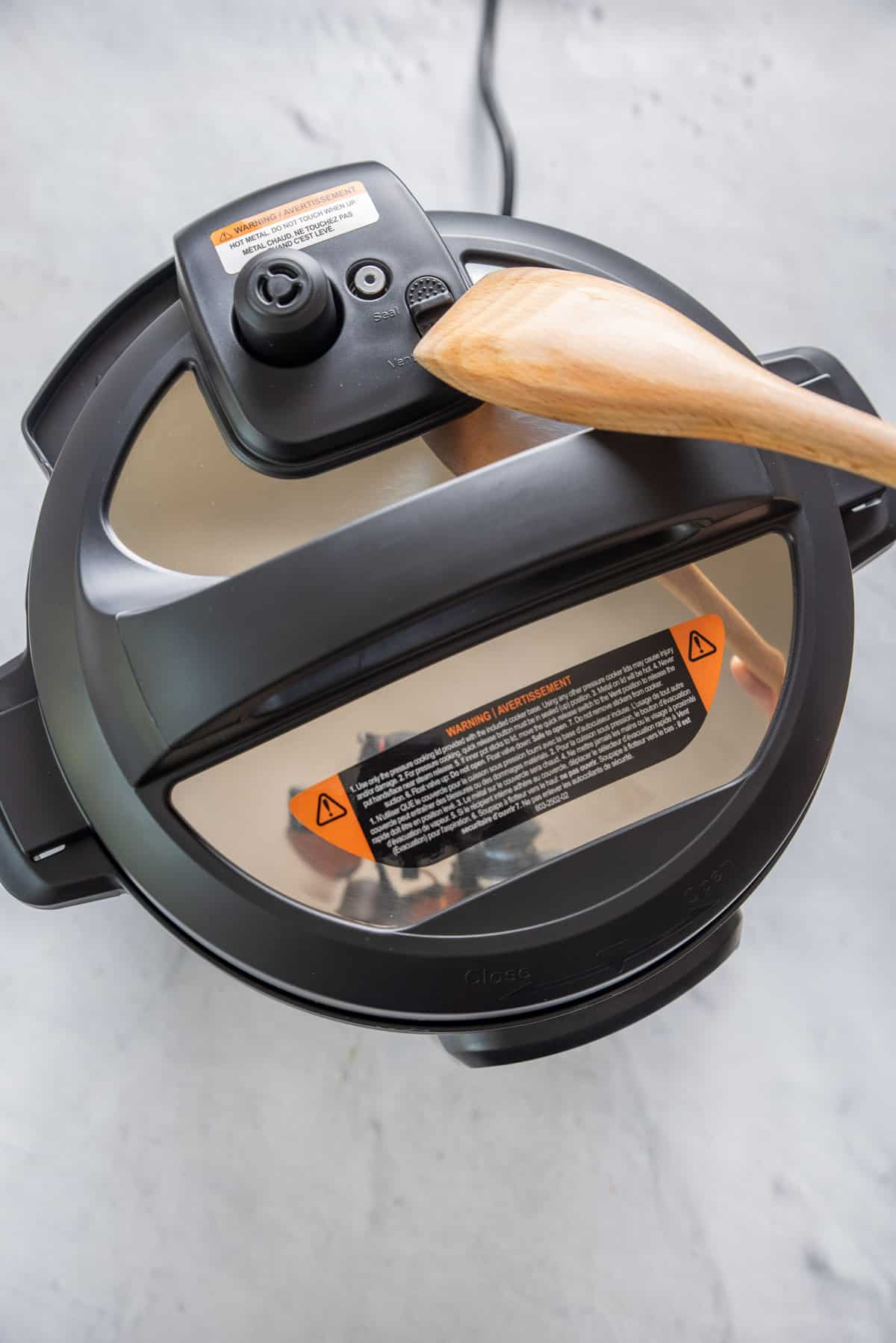 Wooden spoon being used to seal and vent the instant pot