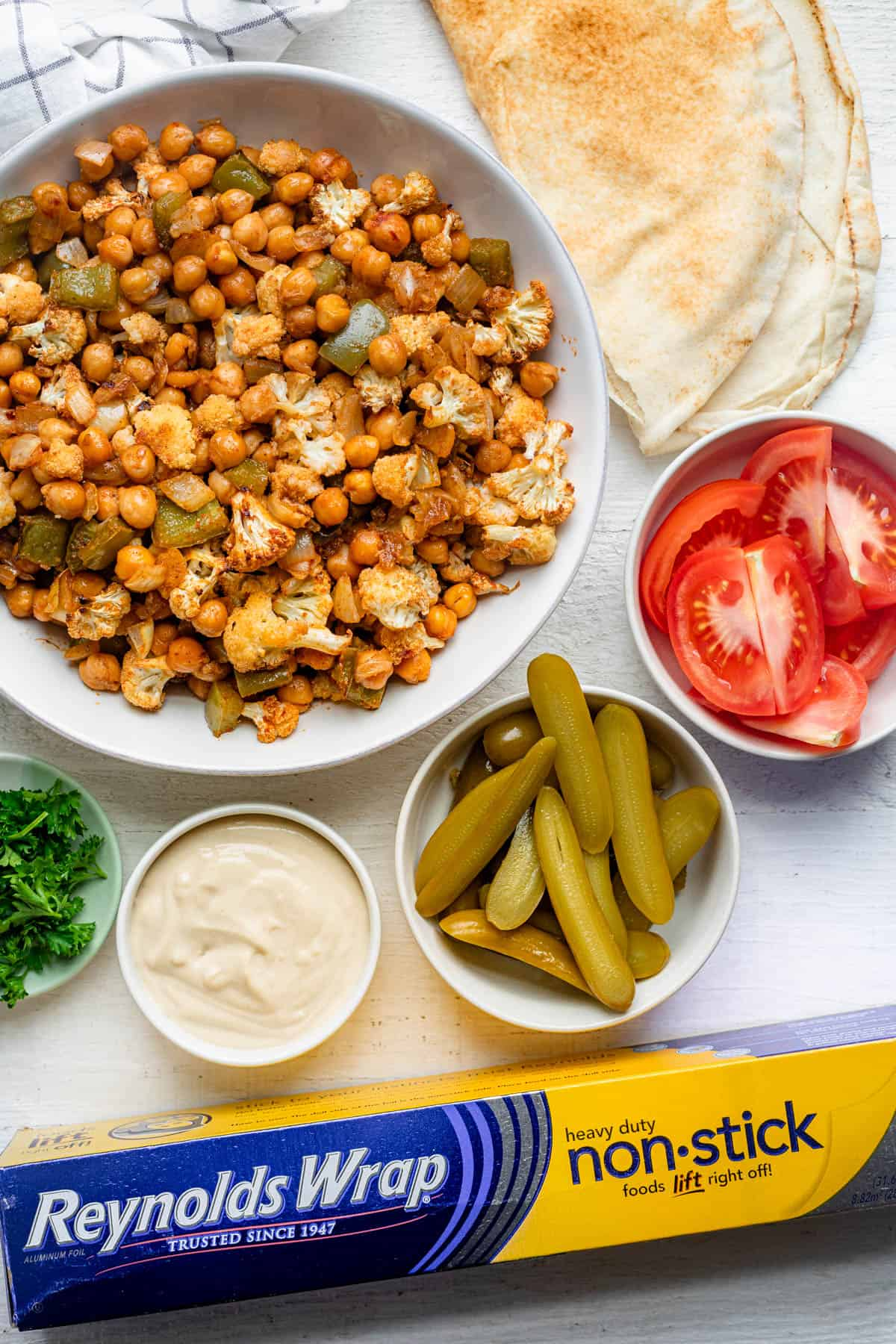 Chickpea shawarma bowl with all the toppings around and Reynolds wrap nonstick foil