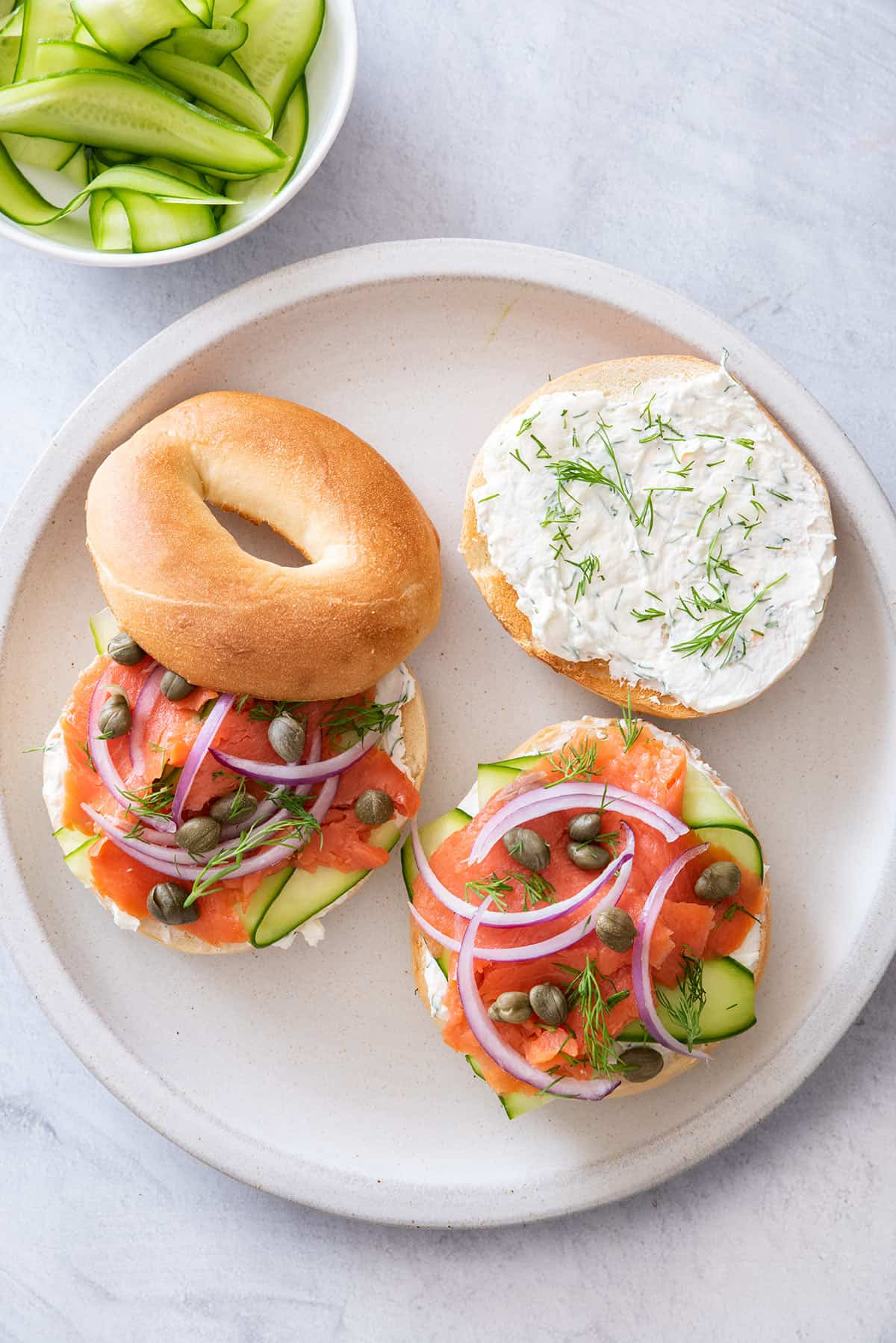 Two smoked salmon bagel sandwiches with a side of extra cucumbers