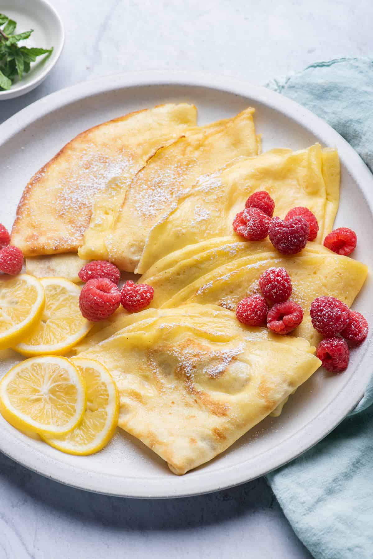 Close up of crepes on plate with raspberries and lemon