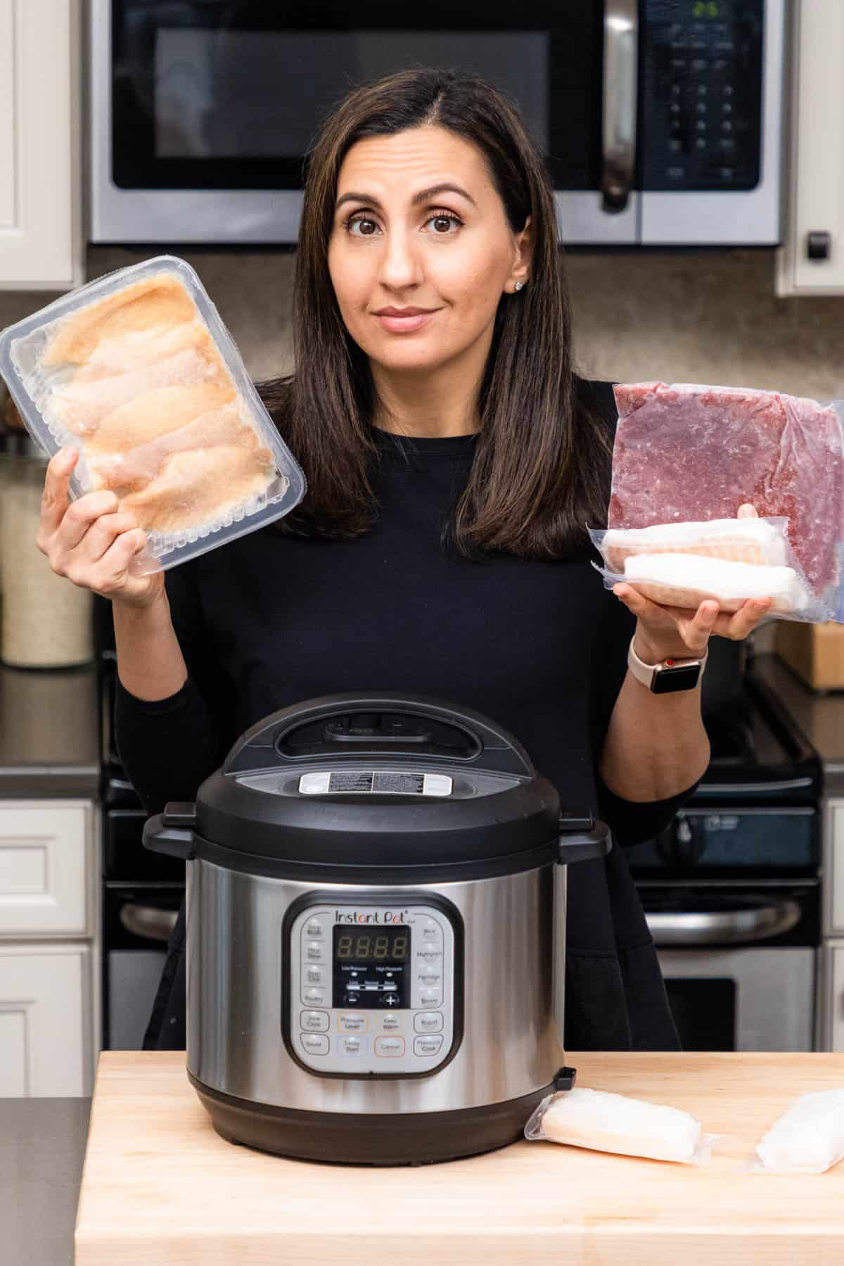 Yumna holding frozen chicken, beef and fish with instant pot