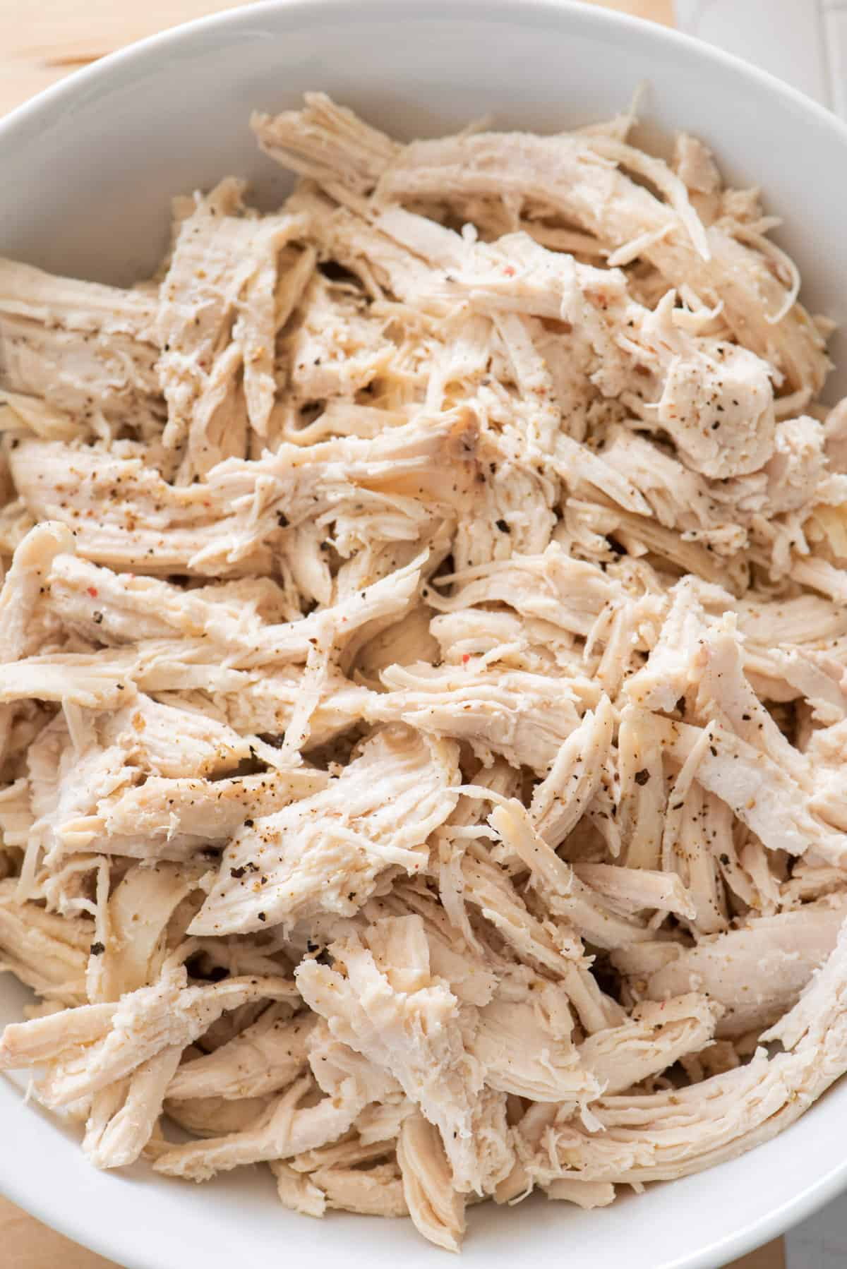 Close up for shredded chicken in a large white bowl
