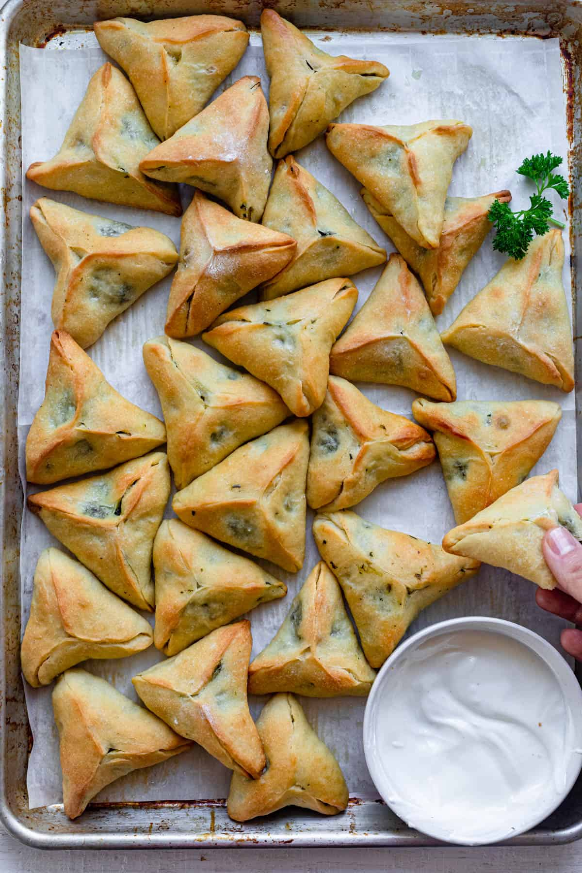 Large tray of spinach fatayer pies served with laban yogurt
