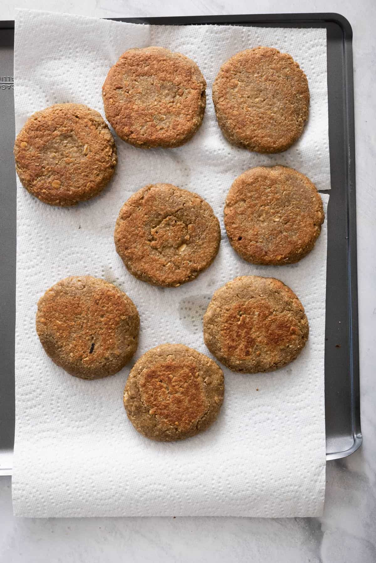 Lentil cakes after frying resting on baking dish lined with paper towel