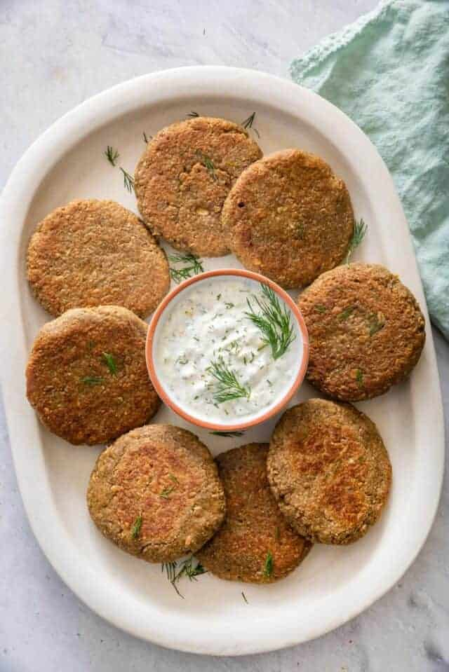 Lentil cakes on serving dish with yogurt dill sauce in the middle