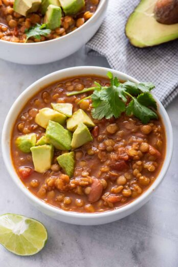 Two bowls of vegan lentil chili with avocado