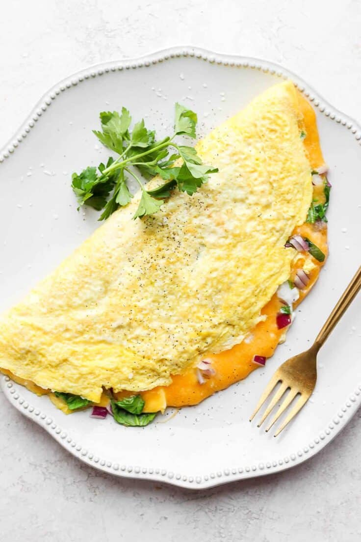 Finished omelette recipe on a plate with parsley on the ide