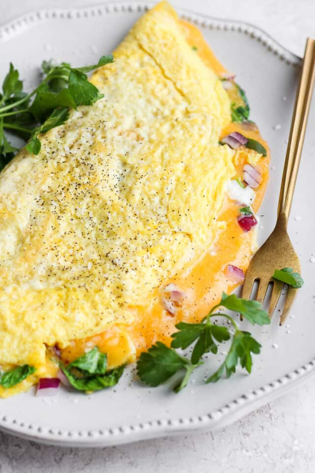 Close up shot of omelette with parsley on the side on a fork