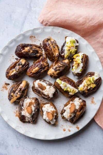 Large white plate of stuffed dates with different flavors