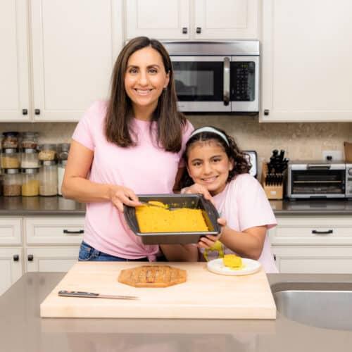 Yumna and Carine holding cake pan - feeding a family
