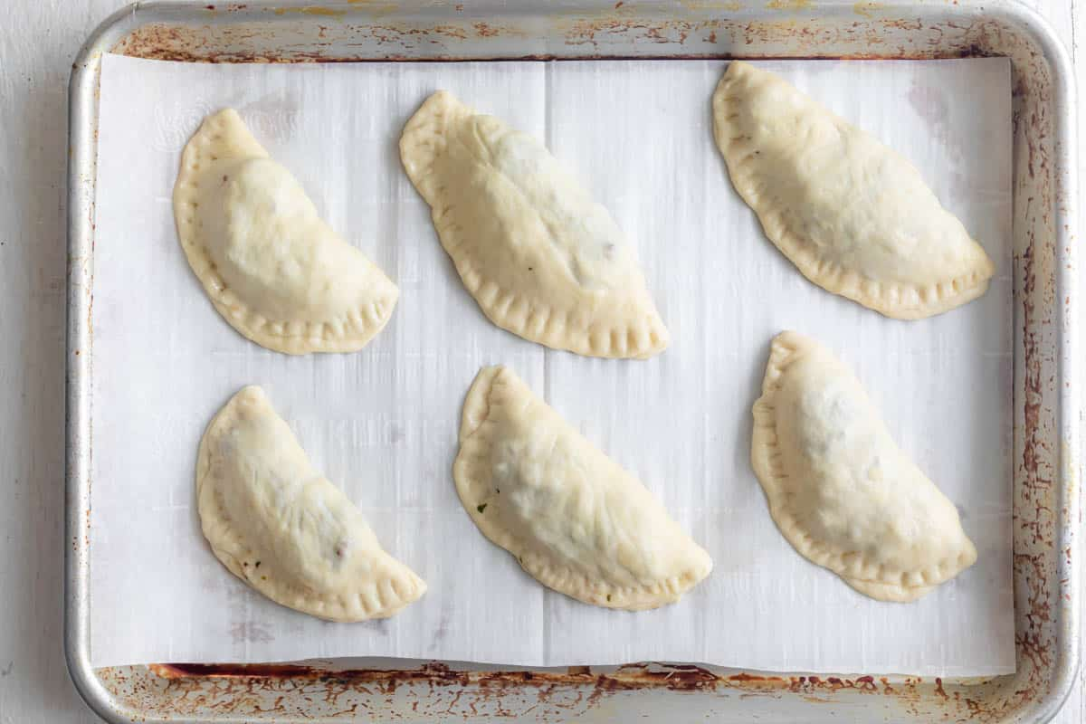 Meat pies on baking dish with parchment paper before baking