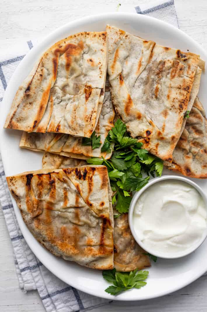 Lebanese meat stuffed pita triangles served on a white platter with a small bowl of yogurt and parsley for garnish