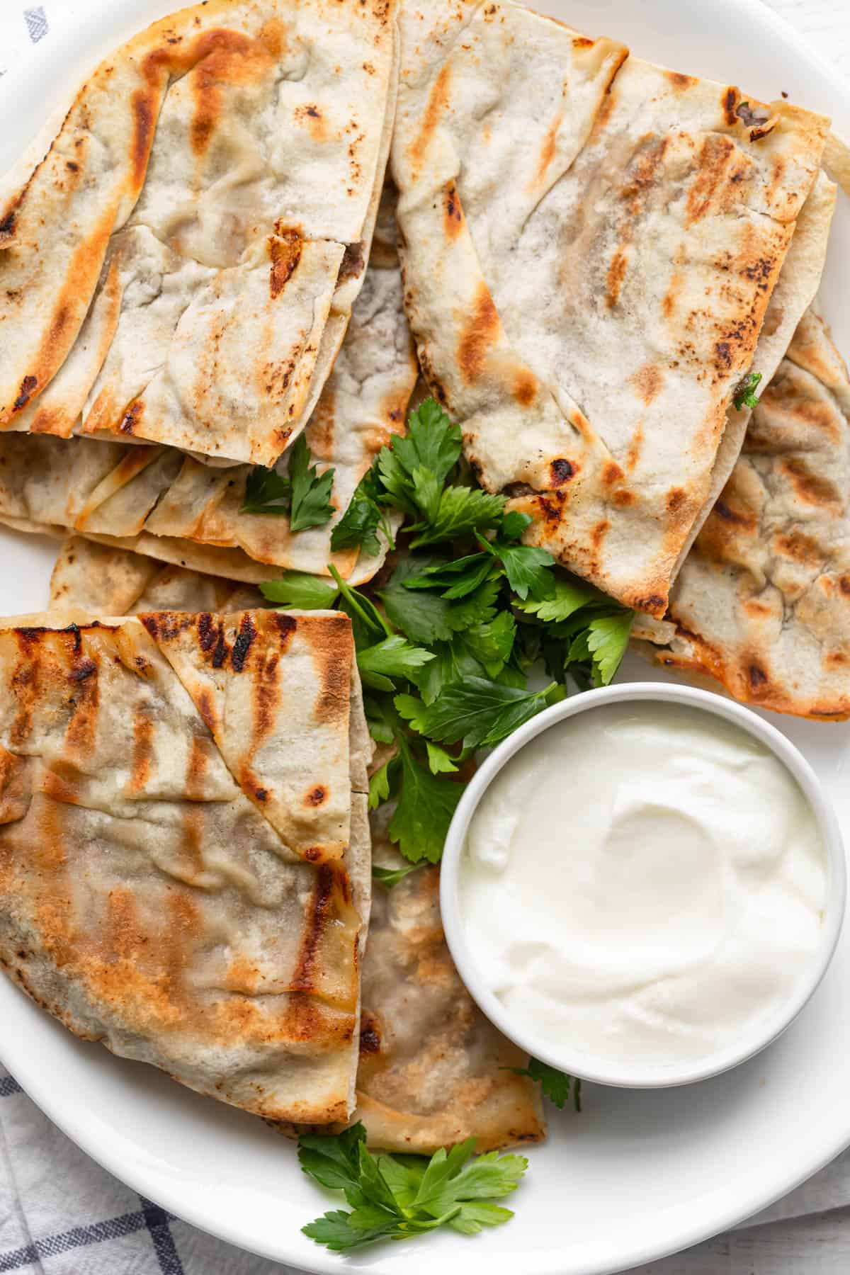 Final serving of the meat stuffed pitas (arayes) with yogurt and parsley