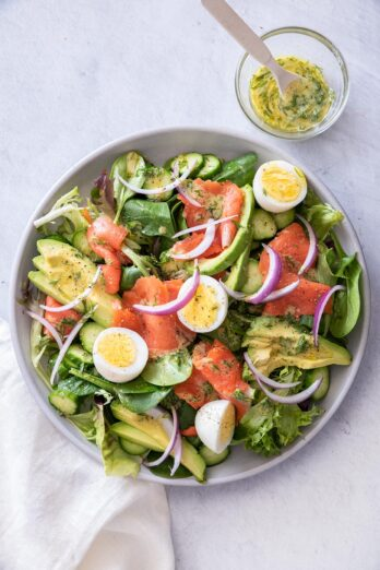 Smoked salmon salad in a large plate with dressing on the side