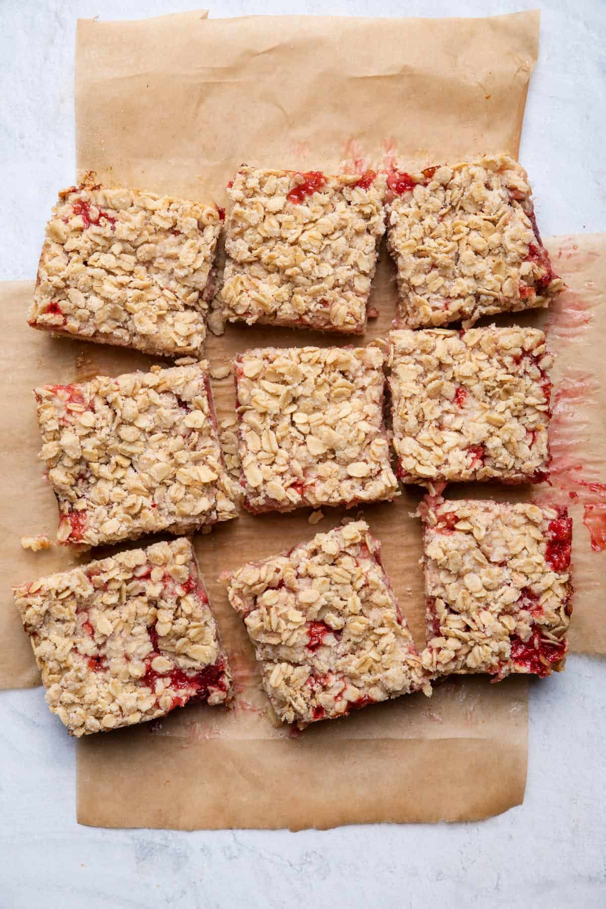 Strawberry oat bars after baking on parchment paper cut into 9 bars
