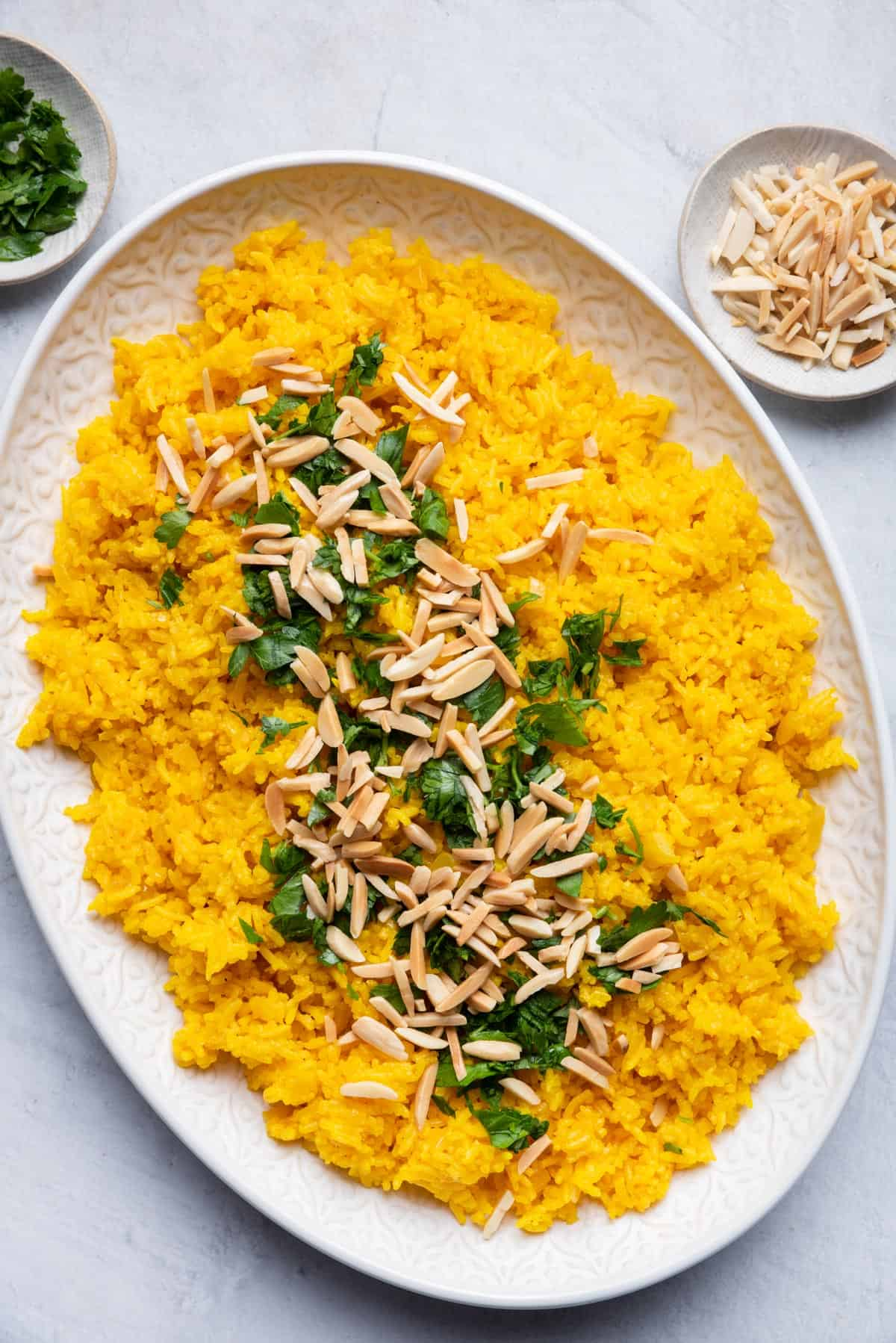 Turmeric rice served in a large platter topped with parsley and almonds