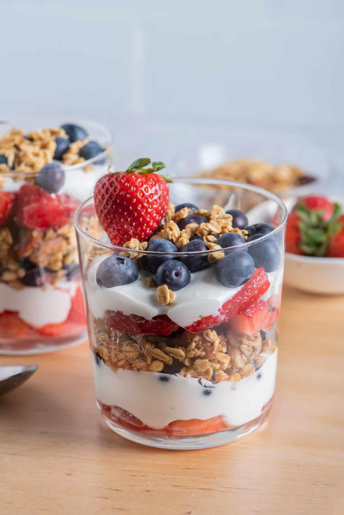 Cup of layered yogurt and fruit parfait with red, white and blue layers including strawberries and blueberries