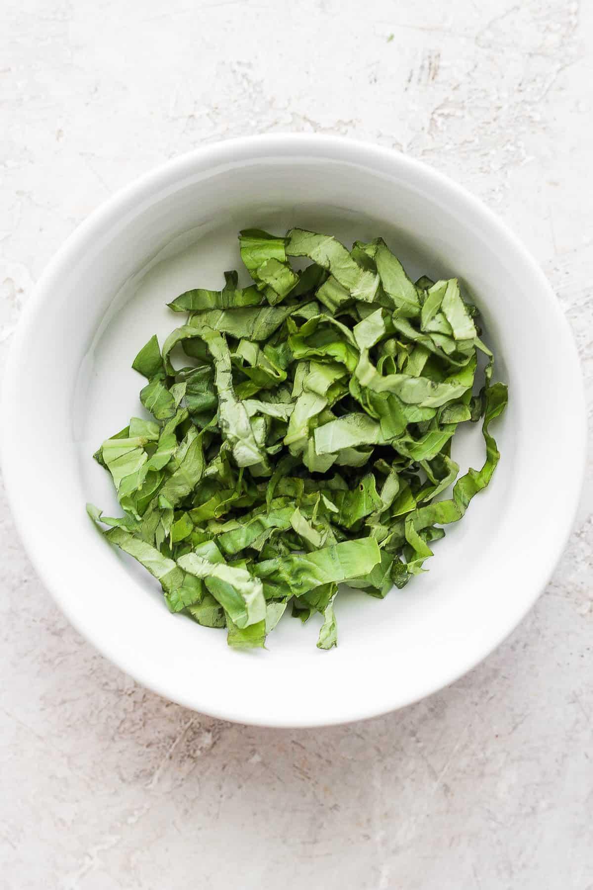 White bowl of chiffonade basil